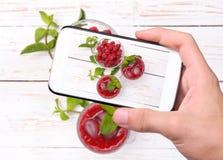 Hands taking photo raspberries drink with smartphone. Instagram Stock Photos