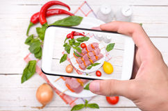 Hands taking photo raw kebab with smartphone royalty free stock images