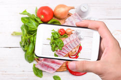 Hands taking photo raw pork rib meat with smartphone. The concept of cooking Stock Image