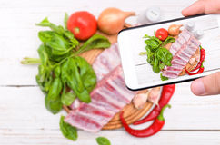 Hands taking photo raw pork rib meat with smartphone. The concept of cooking Royalty Free Stock Photo