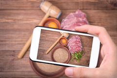 Hands taking photo raw pork schnitzel with smartphone. Stock Images