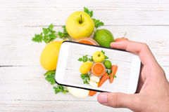 Hands taking photo smoothies with carrots, apple, lemon, parsley with smartphone. Stock Image