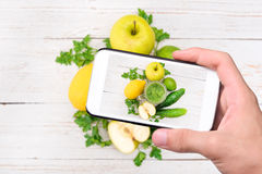 Hands taking photo smoothies with cucumber, apple, lemon, parsley with smartphone. Royalty Free Stock Photos