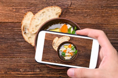 Hands taking photo soup with chicken and vegetables with smartphone. Royalty Free Stock Photo