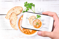 Hands taking photo soup with chicken and vegetables with smartphone. Royalty Free Stock Photos