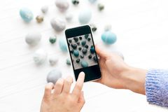Hands taking photo of stylish Easter eggs on white wooden background flat lay on phone. Modern easter eggs painted with natural. Dye in blue and grey marble royalty free stock photos