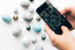 Hands taking photo of stylish Easter eggs on white wooden background flat lay on phone. Modern easter eggs painted with natural. Dye in blue and grey marble royalty free stock photography