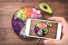 Hands taking photo sushi bowl with smartphone. Stock Photos