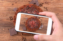 Hands taking photo truffle chocolate cake with smartphone. Royalty Free Stock Photography