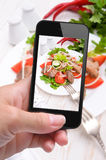 Hands taking photo vegetable salad with meat with smartphone Royalty Free Stock Images