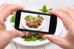 Hands taking photo vegetable salad with meat with smartphone royalty free stock photo