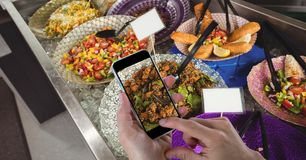 Hands taking picture of food with mobile phone at grocery store royalty free stock images