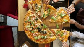 Hands taking pizza cuts from plate on table.