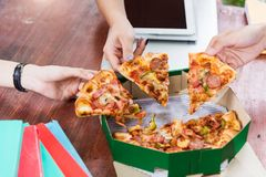 Hands taking pizza slices. From green box stock images