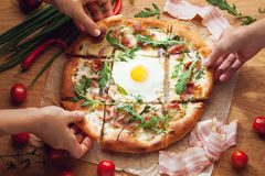 Hands taking slices of fresh pizza Stock Photo