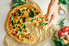 Hands taking slices of pizza. Hand holding slice pizza. Hand taking pizza slices from white wooden background. Pizza and hand close up over white background stock photos