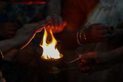 Hands taking warmth of Divine diya holy flame of hindu god worship puja for blessings.  stock photo