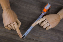 Hands and Tape measure. On a wooden background. construction estimating tools Stock Photos