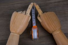 Hands and Tape measure, construction estimating tools. Hands and Tape measure on a wooden background. construction estimating tools Stock Photos