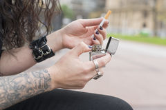 Hands with tattoo holding classic lighter and cigarette. Stock Photos