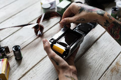 Hands with tattoo installing filmstrip to a camera Royalty Free Stock Photos