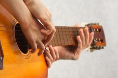 Hands of teacher helping child to play acoustic guitar. Hands of adult helping child to play acoustic guitar royalty free stock photos