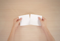 Hands tearing a piece of paper in half blank white flyer brochur Stock Photos