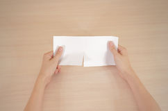 Hands tearing a piece of paper in half blank white flyer brochur Stock Photo