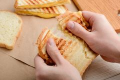 Hands tearing a sandwich apart. Beautiful ruddy stripes on crunchy crust and gooey melted cheese royalty free stock image