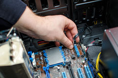Hands of technician installing HDD. On motherboard Stock Image