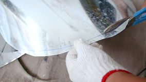 Hands of technician using hard scissor to cutting a sheet of alu zinc for circle layout shape stock footage