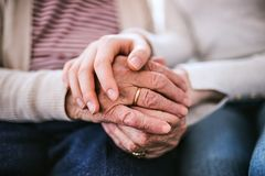 Hands of teenage girl and her grandmother at home. royalty free stock images