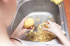 Hands of a teenager boy peeling potatoes with a peeling knife in the kitchen to help parents - children doing homework and cooking royalty free stock image