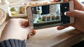 Hands of a teenager make a photo of food on a smartphone. A set of sushi rolls from Japanese cuisine on the background. Of a porcelain teapot for soy sauce and stock video