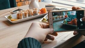 Hands of a teenager make a photo of food on a smartphone. A set of sushi rolls from Japanese cuisine on the background. Of a porcelain teapot for soy sauce and stock footage