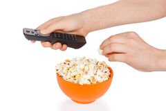 Hands a teenager with popcorn and remote control Stock Photos
