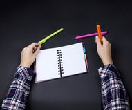 The hands of a teenager on a table with a notepad and pens.  royalty free stock image