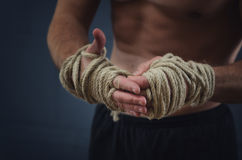 Hands Thai boxer. Close-up of a young Thai boxer hands hemp ropes are wrapped before the fight or training Royalty Free Stock Photos