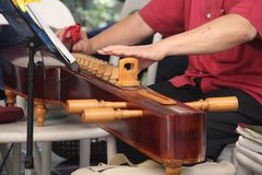 Hands of man playing a zither. Hands of Thai man playing a zither, Thai instument in Bangkok,Thailand Royalty Free Stock Images