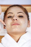Hands of therapist apply cream to face of woman. Concept of care Stock Image