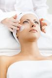 Hands of therapist apply cream to woman face Stock Photography