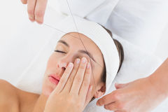 Hands threading beautiful woman's eyebrow Stock Photography