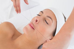 Hands threading beautiful woman's upper lip Royalty Free Stock Image