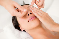 Hands threading beautiful womans eyebrow Stock Image