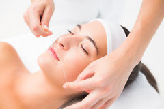Hands threading beautiful womans upper lip Stock Photos