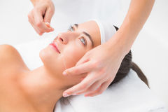 Hands threading beautiful womans upper lip Stock Image