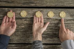 Hands of three business people with Bitcoins laid out in a row Stock Photos