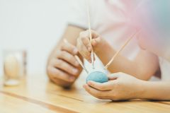 Hands with three painbrushes colouring blue easter egg. Happy family. Easter mood. Focus on the egg. Crop blurred shot of the exciting process of painting stock image