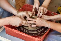 Hands of three people create pot, potter`s wheel. Teaching pottery Royalty Free Stock Images