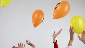 Hands throw up balloons with cryptocurrency logo.